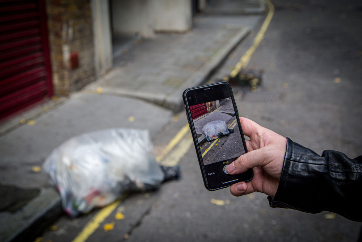 Someone taking a photo of some fly tipping to report on FixMyStreet
