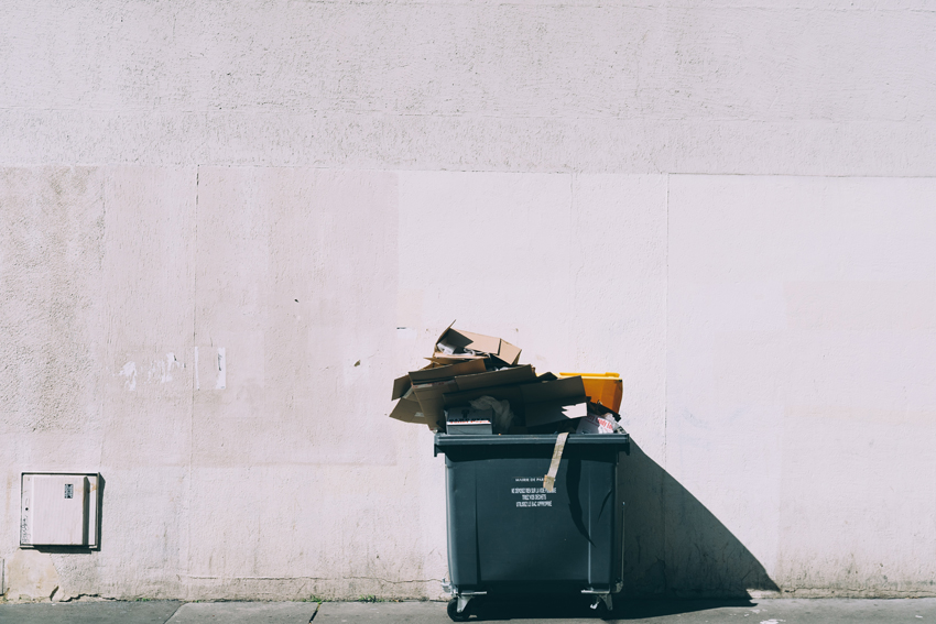 Image by Jilbert Ebrahimi - a wheely bin against a sunny concrete wall