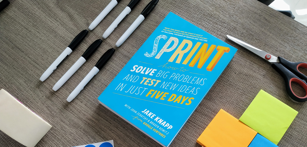 Image by Gautam Lakum - post-it notes and stationary next to a book about sprints.