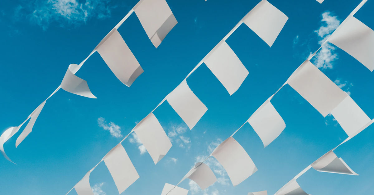 Feature image: White bunting flying against blue sky